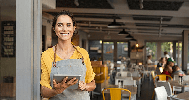 Small business owner smiles at the camera while holding a tablet