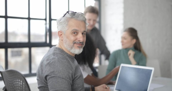 Cheerful male worker sitting with laptop