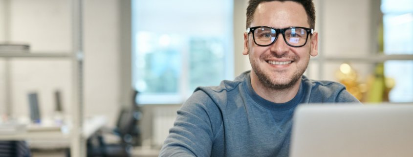 Professional man with glasses smiling while working on a laptop.